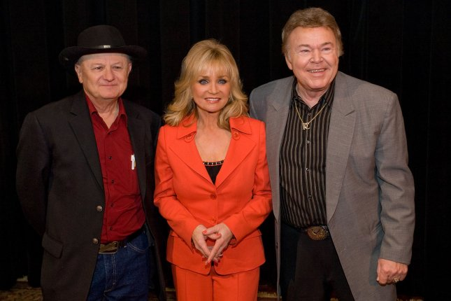 Roy Clark (R), pictured with Charlie McCoy (L) and Barbara Mandrell, died Thursday in Tulsa, Okla. File Photo by Frederick Breedon IV/UPI