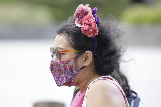 A women wears a face mask to protect from and prevent the spread of COVID-19 as she walks on the grounds of Hudson Yards in New York City on Saturday, August 29, 2020. Photo by John Angelillo/UPI