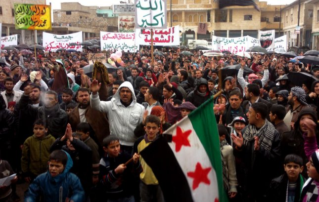 Demonstrators shout slogans as they wave Syrian independence flags during a protest against Syria's President Bashar Al-Assad, after Friday prayers in Idlib, Syria, on February 17, 2012. UPI