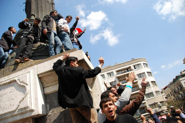 Syrian anti-government protesters shout slogans during a demonstration in Damascus on March 25, 2011, calling for the ouster of Syrian President Bashar al-Assad. Ten years later, Assad remains in power. File Photo by Ali Bitar/UPI