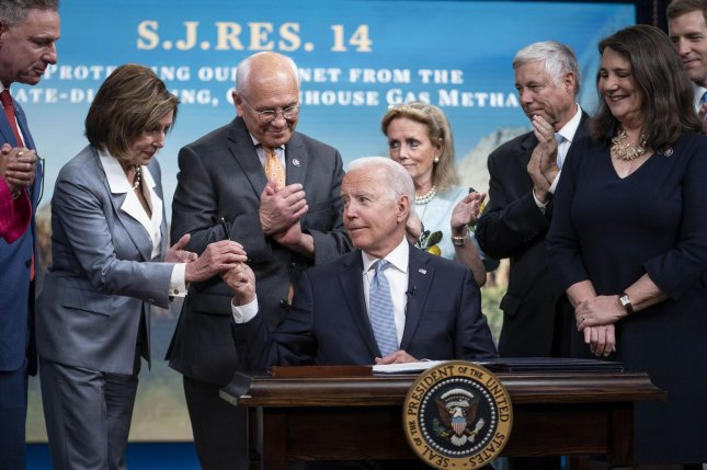 President Joe Biden signs S.J.Res.14, one of the three Congressional Review Act bills, into law in Washington, D.C., on Wednesday, and hands the pen he used to House Speaker Nancy Pelosi. Photo by Sarah Silbiger/UPI