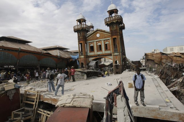 People stand on the remains of a market in Port-au-Prince, Haiti on January 19, 2010, after a 7.0 magnitude earthquake caused severe damage on January 12. UPI/Anatoli Zhdanov