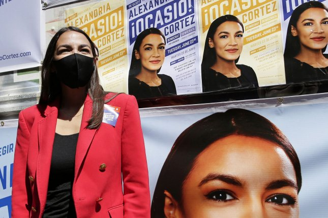 Rep. Alexandria Ocasio-Cortez, D-N.Y., stands next to a campaign truck covered with her photos on Tuesday as she prepares to speak to the media on New York's primary election day. Photo by John Angelillo/UPI