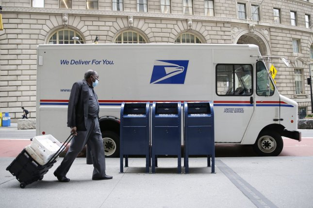 A man pulls crates of mail to a U.S. Postal Service truck in New York City. U.S. Postmaster General Louis DeJoy said changes he was brought in to make at the USPS will be suspended until after the election. Photo by John Angelillo/UPI