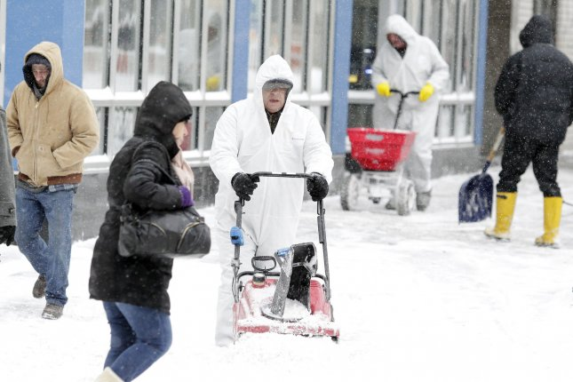 People walk by workers who shovel and lay salt on the sidewalks in New York City on January 3, 2014. (File/UPI/John Angelillo)