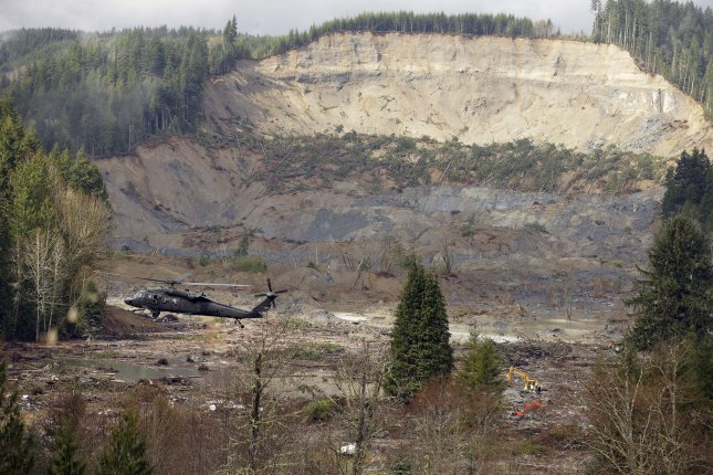 A military search and rescue helicopter hovers over the debris field on March 27, 2014 in Oso, Washington. UPI/Ted Warren/Pool