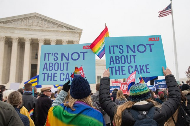 Demonstrators hold up signs outside the U.S. Supreme Court in 2017 during arguments in a case involving a baker who didn't want to make cakes for gay weddings. File Photo by Erin Schaff/UPI
