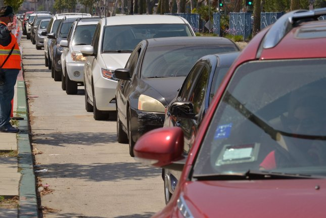 Cars idle for miles in line for food being distributed to residents impacted by the COVID-19 crisis at Jordan High School in Long Beach, Calif., on May 9. Photo by Jim Ruymen/UPI