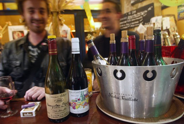 People celebrate the official launch of the Beaujolais Nouveau wine at a cafe in Paris. (UPI Photo/Eco Clement)