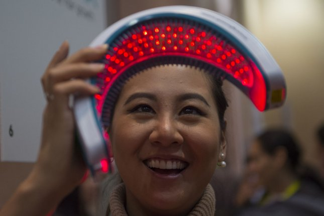 Attendee Kimberly Wang looks at the HairMax LaserBand laser hair growth device at CES Unveiled on Monday, ahead of CES 2016, a trade show of consumer electronics, in Las Vegas. Photo by Molly Riley/UPI