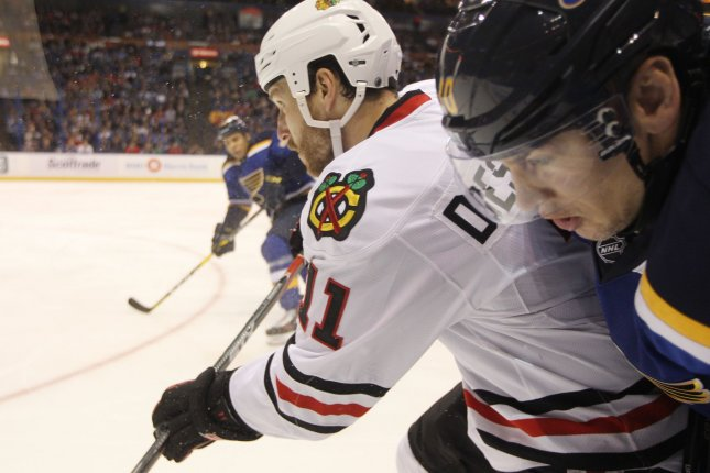 Chicago Blackhawks Andrew Desjardins checks St. Louis Blues Scottie Upshall into the boards in the first period at the Scottrade Center in St. Louis on December 17, 2016. Photo by Bill Greenblatt/UPI