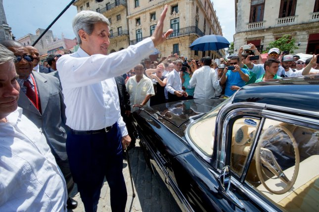 Then-U.S. Secretary of State John Kerry waves to Cubans in front of a vintage Impala in the Plaza de San Francisco after a ceremony reopening the U.S. embassy in Havana during the Obama administration. The State Department now is restricting Cubans' travel to the United States by reduce the B2 tourist visa validity to three months with a single entry from five years of multiple trips. File Photo by U.S. Department of State/UPI