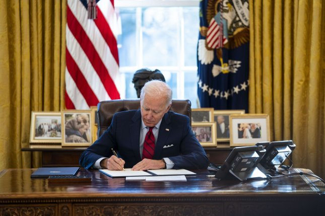 President Joe Biden signs executive actions strengthening Americans' access to quality, affordable healthcare in the Oval Office of the White House on Thursday. Pool Photo by Doug Mills/UPI