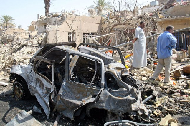 A burned out car is seen among rubble at the site of a bombing in Baghdad, Iraq. (File/UPI Photo)
