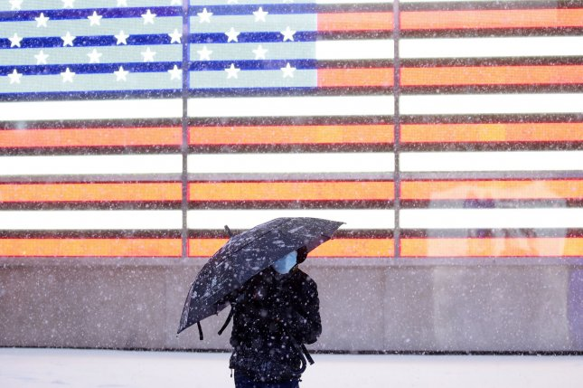 A pedestrian walks by a lighted American Flag in New York City's Times Square on Monday as snow falls. A major nor'easter threatens to dump as much as 2 feet of snow on parts of the Tri-State area over the next two days. Photo by John Angelillo/UPI