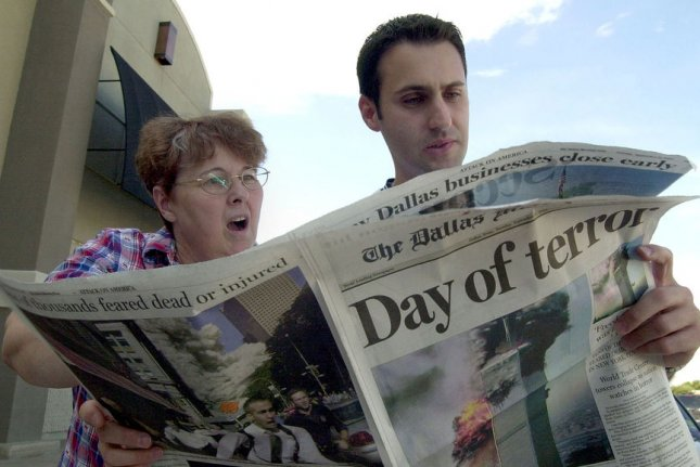 Two pedestrians react to newspaper photographs depicting the terrorist attacks in New York City and Washington, D.C., in Dallas on September 11, 2001. File Photo by Ian Halperin/UPI