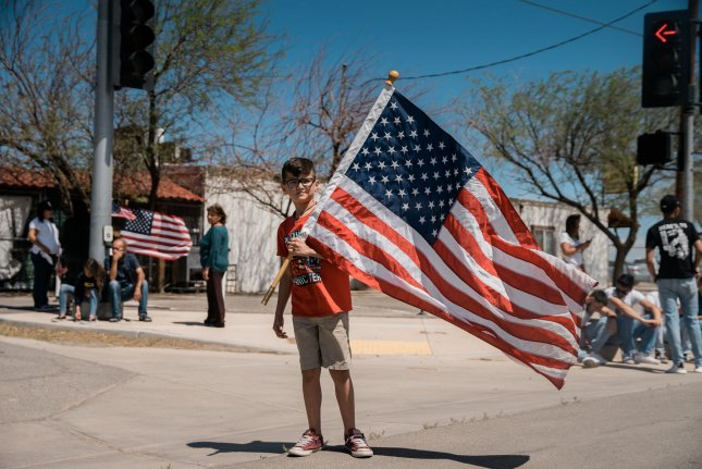 A young boy holds an American flag during a trip by President Donald Trump to Calexico, California, on April 5. File Photo by Ariana Drehsler/UPI