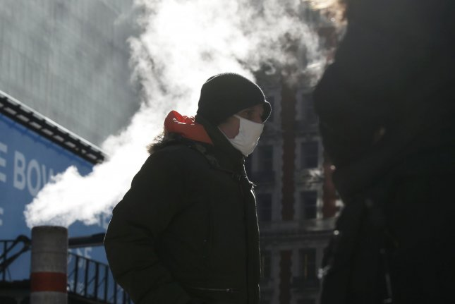 A masked pedestrian walks through Times Square in New York City on Thursday. In nearby Newark, N.J., residents are being ordered to stay home for 10 days starting the day before Thanksgiving.  Photo by John Angelillo/UPI