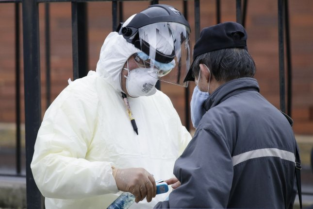 A medical professional wearing protective equipment performs a test for coronavirus on a patient at Elmhurst Hospital Center on Tuesday, March 31, 2020, in New York City. Clinical trials have begun for remdesivir, an Ebola drug that has already been given to a limited number of patients hospitalized with COVID-19, on a compassionate use basis. Photo by John Angelillo/UPI