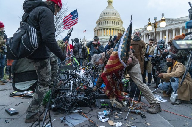 Rioters loyal to former President Donald Trump destroy video gear at the U.S. Capitol as hundreds of others breach the security perimeter at the building on January 6 to disrupt the certification of Joe Biden as the winner of the 2020 U.S. presidential election. File Photo by Ken Cedeno/UPI