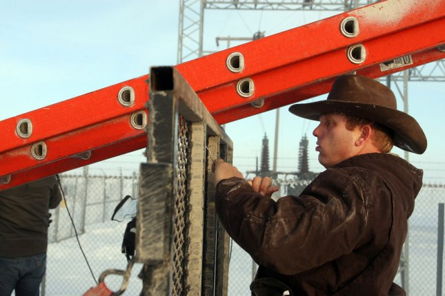 Malheur National Wildlife Reserve protestors, brothers Ammon and Ryan Bundy, entered not guilty pleas in a separate 2014 case. The pleas were entered on their behalf, after the brothers refused in court Friday. The brothers were transferred from Oregon to Las Vegas where they faced felony charges in relation to a standoff with federal agents at their father's ranch in 2014. Pictured: Ammon Bundy unties a ladder used to remove two FBI surveillance cameras found at a power station near the Malheur National Wildlife Reserve on January 15 in Burns, Oregon.  Photo by Jim Bryant/UPI