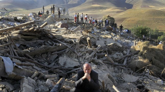 An Iranian man sits on top of his destroyed house as rescue teams in the background search for victims in the rubble of destroyed buildings in Varzaqan, Northeast of Tabriz, Iran. A 6.2 magnitude earthquake struck Varzaqan, August 11, killing hundreds and injuring thousands. UPI/Maryam Rahmanian