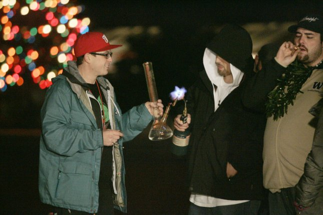 Brian Workman, left, holds a pipe full of marijuana oil for Randy Spencer, center, to lite with a blowtorch during a public consumption marijuana rally on December 6, 2012 in Seattle. Despite the new law's ban on public marijuana use which is subject to a fine of about $50. In November, Washington state jumped into history becoming the first state along with Colorado to reject federal drug-control policy and legalize recreational marijuana use. (File/UPI/Jim Bryant)