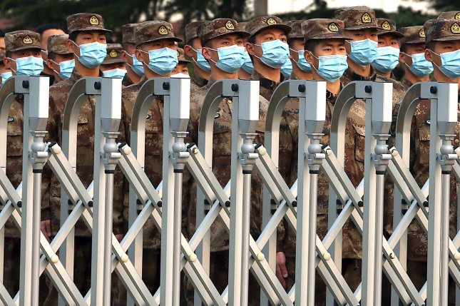 Chinese soldiers stand in formation as they wait to march back to their barracks in Beijing on March 19. Photo by Stephen Shaver/UPI