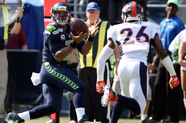 Seattle Seahawks quarterback Russell Wilson (3) catches a pass in front of Denver Broncos safety Rahim Moore (26) on September 21, 2014. UPI/Jim Bryant
