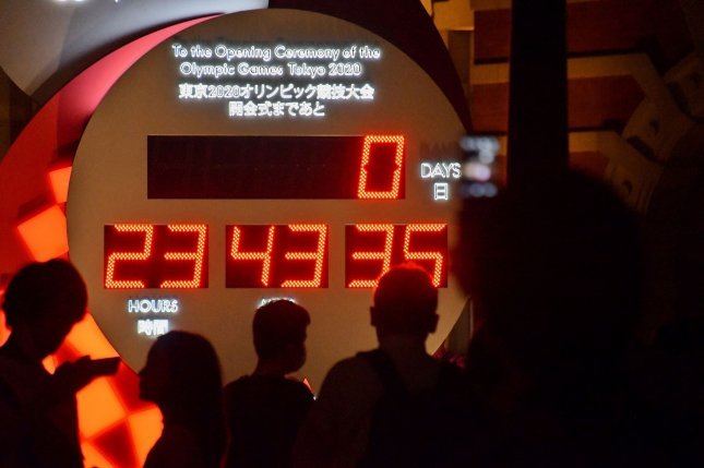 Pedestrians take photos of the countdown clock for the Summer Olympics at Tokyo Station on Thursday. Photo by Keizo Mori/UPI
