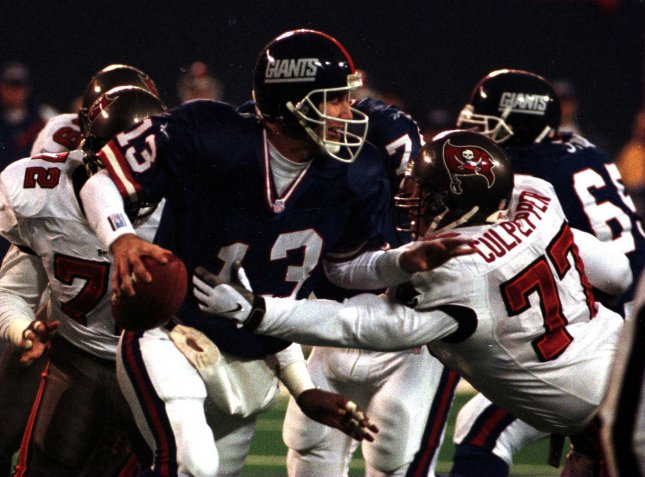 New York Giants #13 Danny Kanell tries to pass despite blocking efforts from Tampa Bay Buccaneers # 77 Brad Culpepper during November 30th 1st half football action at Meadowlands Stadium in New Jersey in 1997. UPI/John Angelillo