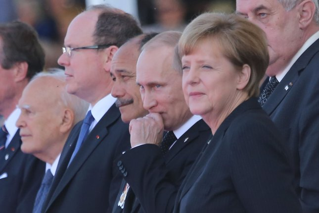 Russian President Vladimir Putin (2nd from R) and German Chancellor Angela Merkel arrive at Sword Beach in Ouistreham to attend the international ceremony commemorating the 70th anniversary of the D-Day landings in the Normandy region of France on June 6, 2014. UPI/David Silpa