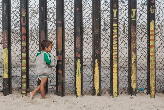 A child migrant looks through the border fence into the United States at Playas de Tijuana in Tijuana, Mexico. File Photo by Ariana Drehsler/UPI