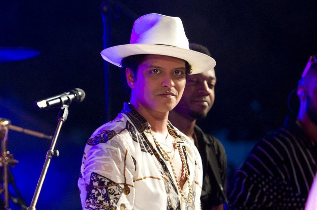 Performer Bruno Mars looks on as U.S. President Barack Obama, accompanied by first lady Michelle Obama, speaks at the White House in Washington, D.C. on July 4, 2015. Pool photo by Ron Sachs/UPI