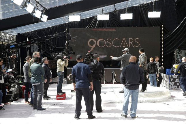 Workers stand on a red carpet protected by plastic as preparations continue for the 90th annual Academy Awards in Los Angeles on March 3. Photo by John Angelillo/UPI