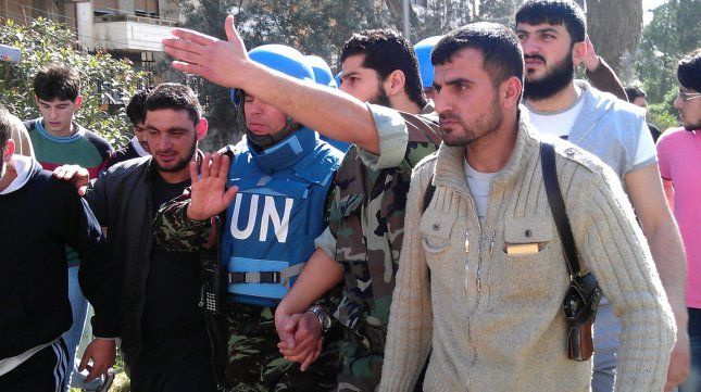 Syrian Abdul Razzaq Tlas, leader of the opposition Katibat al-Faruq, points the way as he walks with Moroccan UN observer, Colonel Ahmed Himmiche (C), during the United Nations monitors visit to the restive city of Homs, Syria on April 21, 2012. UPI/Khaled Tallawy