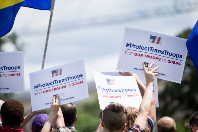 Demonstrators hold up signs in support of transgender troops at a press conference on Capitol Hill calling on President Trump to reverse his new policy on transgender troops in the military in Washington, D.C., on July 26. File Photo by Erin Schaff/UPI
