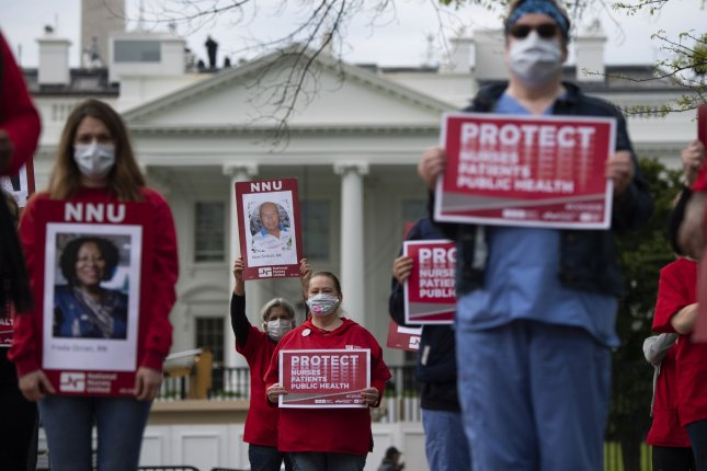 Nurses hold photos of fellow nurses who have died from COVID-19 during a protest on April 21 at the White House, to demand the Trump administration provide more protective equipment for healthcare workers during the coronavirus pandemic. Photo by Kevin Dietsch/UPI