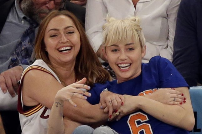 Miley Cyrus (R) and sister Brandi Cyrus at the New York Knicks and Cleveland Cavaliers game on Saturday. Photo by John Angelillo/UPI