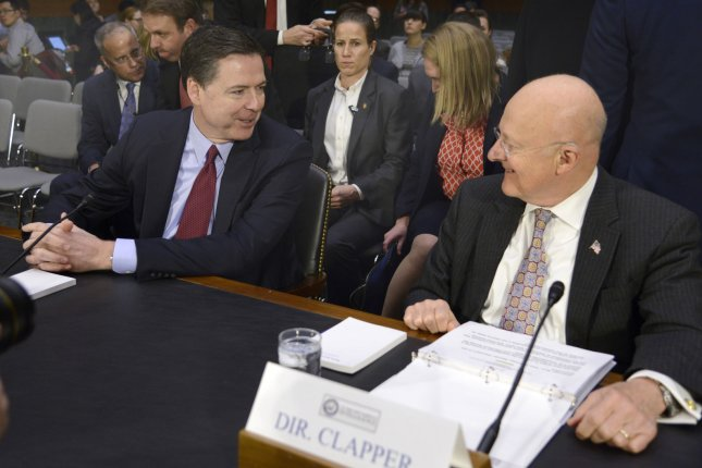 Director of National Intelligence James Clapper (R) chats with FBI Director James Comey on Tuesday before the Senate Intelligence Committee, which heard testimony regarding the U.S. intelligence community's belief that Russia hacked Democratic and Republican organizations last year in an attempt to sway the election in Donald Trump's favor. Photo by Mike Theiler/UPI