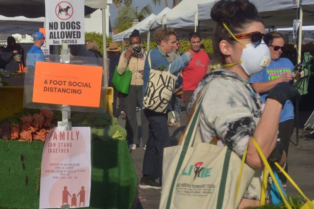 Farmer's market shoppers are unable to maintain a 6-foot social distancing recommended on signs posted at the Larchmont Village market in Los Angeles on Sunday. File Photo by Jim Ruymen/UPI