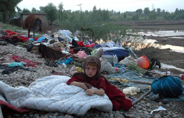 A young girl sits near her home with some of her family's belongings after recent heavy flooding in Nowshera, northwestern Pakistan, on August 2, 2010. Rescue workers and troops in northwest Pakistan struggled to reach thousands of people affected by the country's worst floods since 1929. UPI/Sajjad Ali Qurseshi
