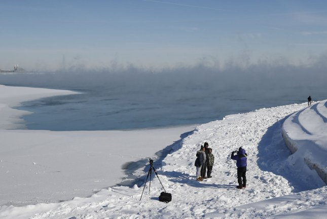 Steam rises from Lake Michigan in Chicago on January 31 as people take pictures after the polar vortex brought abnormally cold temperatures to the Midwest. Researchers say that future winters will be both warmer and colder as climate change continues to shift weather patterns. File Photo by Blake Clark/UPI