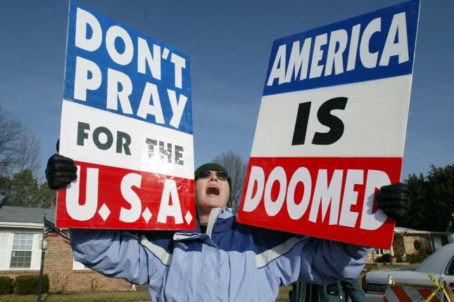 A protester with the Westboro Baptist Church of Topeka, Kan., chants as the funeral procession for U.S. Army Pvt. Peter Navarro pulls up to the St. Clare of Assisi Catholic Church in Ellisville, Mo., on December 23, 2005. On March 2, 2011, the U.S. Supreme Court ruled 8-1 that the anti-gay Kansas church had a constitutional right to stage a peaceful protest at the funeral of a U.S. Marine killed in Iraq. File Photo by Bill Greenblatt/UPI