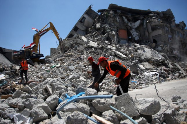 Palestinian workers and machines remove the rubble of destroyed towers and houses in Gaza City, following the fighting between Israel and militants in Gaza City on June 6. Photo by Ismael Mohamad/ UPI