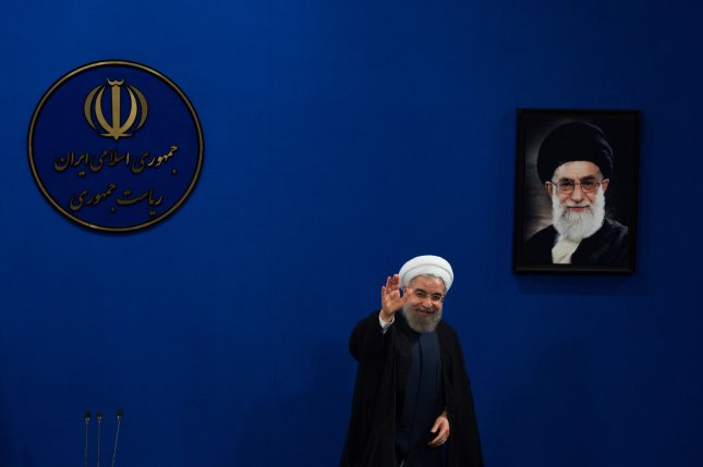 Iran's President Hassan Rouhani waves to reporters next to a portrait of supreme leader Ayatollah Ali Khamenei as he leaves at the end of a press conference in Tehran last August. Since he took office in 2013, at least 2,300 men and 66 women have been executed in Iran, many of them hanged in public. File Photo by Ali Mohammadi/UPI