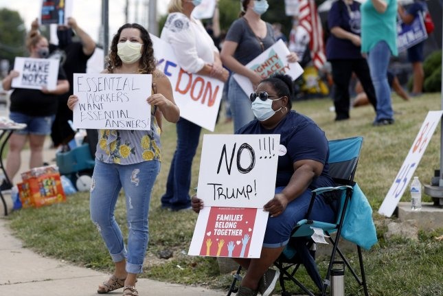 Activists wear face masks and hold protest signs on Thursday along a street in Clyde, Ohio, prior to a visit by President Donald Trump. The president toured a Whirlpool plant and delivered an address on American manufacturing and the economy amid the pandemic. Photo by Aaron Josefczyk/UPI