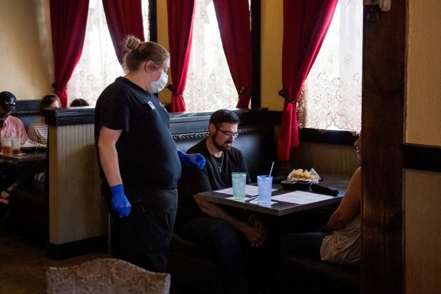 Customers have lunch at El Toro Mexican restaurant in Clute, Texas, as an employee works while wearing a mask and gloves in May. Photo by Trask Smith/UPI