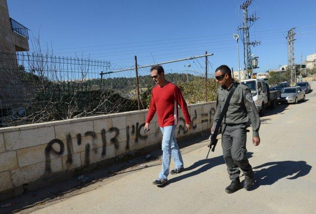 An Israeli border police walks past anti-Arab, racist graffiti spraypainted on a wall during a Price Tag attack by Jewish extremists in the Sharafat neighborhood in Jerusalem, Israel, February 19, 2014. The graffiti reads No coexistence and Arabs = Thieves. More than 30 Arab vehicles had their tires slashed during the night during the Price Tag attacks which are considered a direct response by far right-wing Israelis to peace talks with the Palestinians. UPI/Debbie Hill