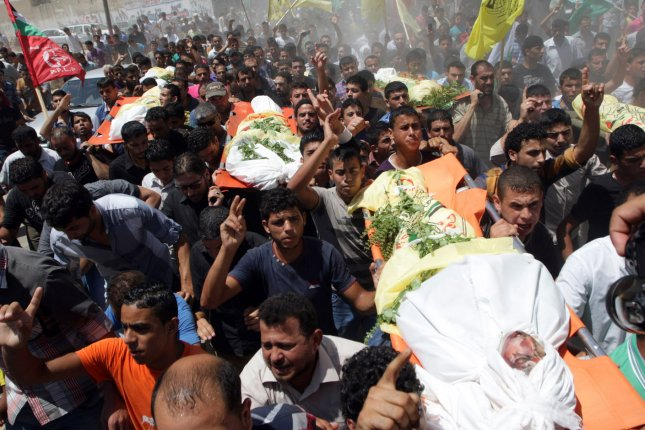 Relatives and friends mourn during a funeral in Khan Yunis, in the Gaza Strip, on July 9, 2014. The father and his six sons were all killed in an Israeli air strike that apparently targeted their home in response to Hamas firing rockets into Israel. UPI/Ismael Mohamad